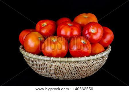 Tomatoes in a rattan bowl isolated against a black background