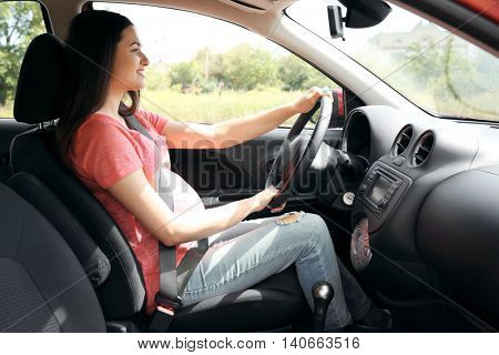 Pregnant woman driving car. Safety drive concept