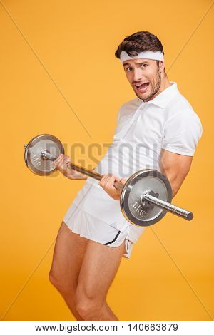 Amusing young sportsman shouting and holding heavy barbell over yellow background