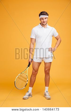 Full length of attractive young man tennis player standing and holding racket over yellow background