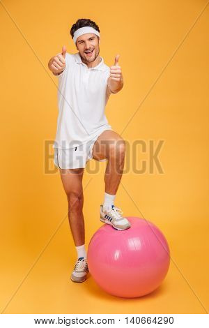 Young handsome sportsman with one foot on fitness ball showing thumbs up isolated on the orange background