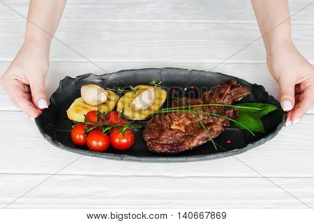 New meat meal presentation, white wooden background. Chef hands holding plate with grilled steak and vegetables, author recipe showing