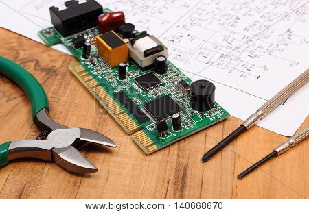 Printed circuit board with electrical components precision tools and construction drawing of electronics on wooden board accessories for engineer jobs technology