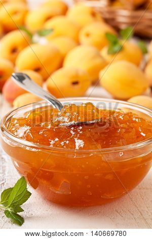 Apricot jam in a glass bowl fresh apricots in a basket on a light wooden background
