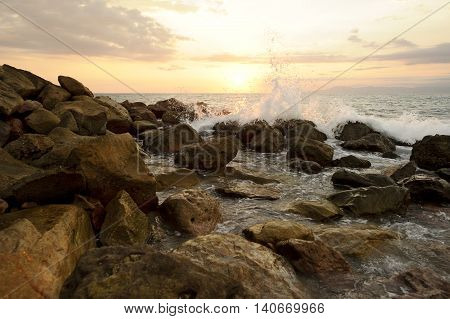 Ocean wave slash is a sunset seascape with rocks near the shore as a breaking wave sprays up in the air.