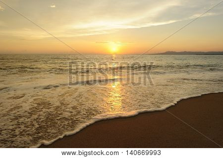 Ocean sunset is a brightly beach scene with the sun setting on the ocean horizon as a gentle wave rolls along the sandy shoreline.