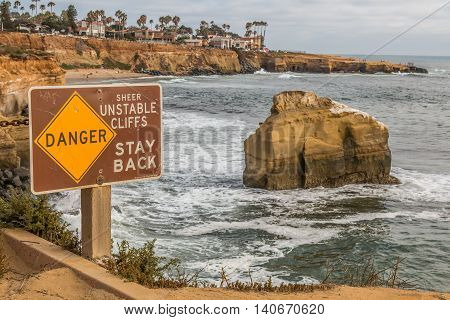 Close-up view of danger sign with Bird Rock in background at Sunset Cliffs in San Diego, California.