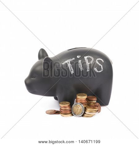 Word Tips written with chalk on a black ceramic piggy bank coin container next to a pile of euro coins, composition isolated over the white background