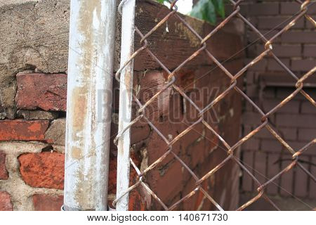 A chain link fence with a brick wall.