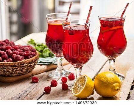 On wooden boards are ice cold beverage glasses with red raspberry lemon cocktail . Alcohol country cocktail beverage number three hundred and eighteen with mint. Group cocktail on edge of table.