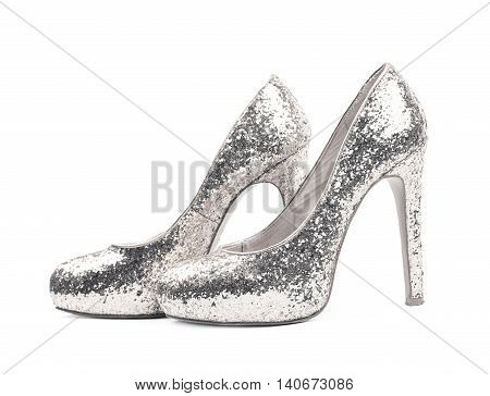 Pair of shining silver high-heeled footwear shoes, composition isolated over the white background