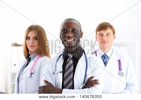 Group of smiling friendly medicine doctors look in camera portrait standing in row. High level service best treatment 911 healthy lifestyle therapeutist consultation physical emergency concept