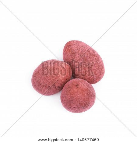 Pile of almond nuts coated with the red colored chocolate, composition isolated over the white background