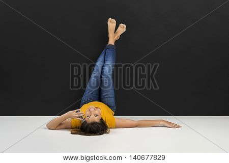 Beautiful woman lying in the floor and talking at phone