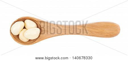 Wooden serving spoon full of the white chocolate coated nut candies isolated over the white background