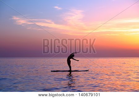 Silhouette of a yoga teacher over sunset background doing asanas, balancing on the sup board, enjoyi