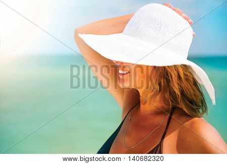 Beautiful middle aged woman in a big white hat tanning on the beach. Beauty female portrait over blue ocean background. Summer holidays, vacation concept. Relaxing on resort under the Hot Sun. Suntan