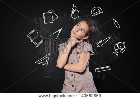 Small girl near blackboard thinking. Thoughtful, pensive child consider something. Smart schoolgirl studio portrait near chalkboard with education icons. Studying school subjects concept.