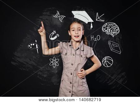 Small girl in imaginary graduation cap has an idea. Child shows finger up as eureka sign. Smart schoolgirl studio portrait near chalkboard with education icons. Studying and getting knowledge concept.