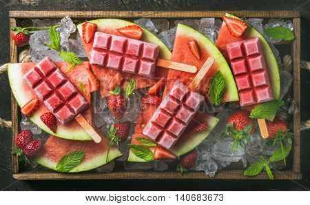 Homemade watermelon strawberry popsicles on ice served with fresh fruits and mint leaves in wooden tray, top view, horizontal composition