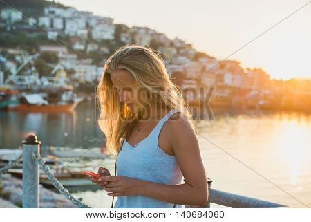 Young blond tourist woman texting message at sunset, harbour of Alanya at background. Turkey, Mediterranean region