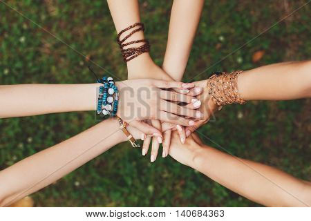 United hands of young females, top view. Stylish hands of girlfriends in boho hippie bracelets at green grass background. Togetherness and support, youth fashion and active lesiure. Women friendship