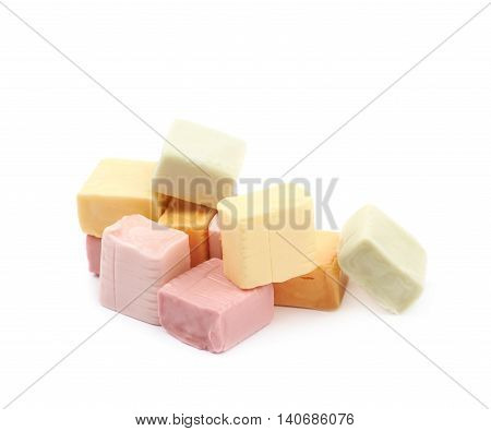 Pile of multiple colorful chewing cuboid-shaped candy gums isolated over the white background