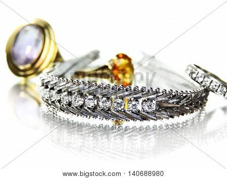 Jewelry, arrangement of gemstones, bracelet and diamond ring, isolated on white.
