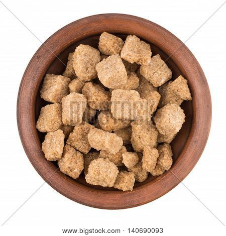 Cubes of whole cane sugar in bowl isolated on the white background. Top view.