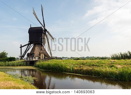 Wooden hollow post mill with a thatched under tower near the village of Molenaarsgraaf Alblasserwaard South Holland Netherlands. The now restored mill dates from about 1655 and is now a protected national monument.