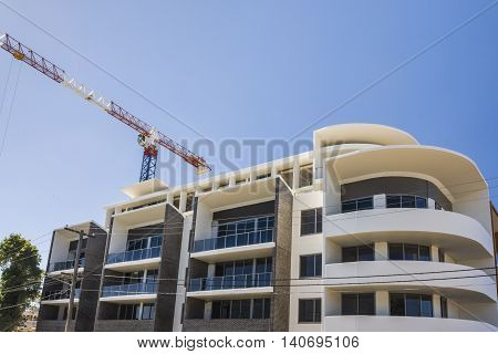 Modern Building Finishing With A Crane Under Blue Sky