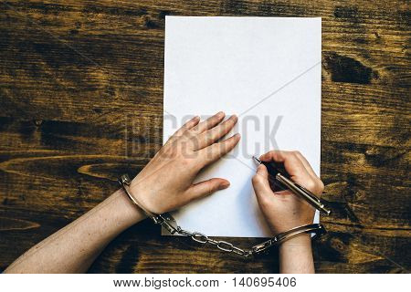 Female hands cuffed signing confession top view of police investigator detective desk