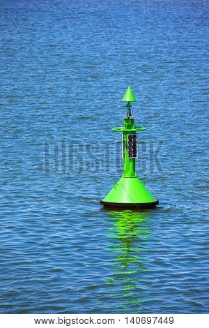 Fairway with green buoy in a sea.