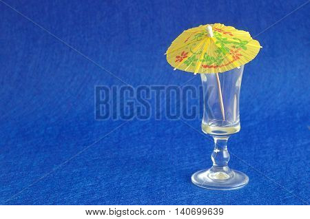 A yellow cocktail umbrella displayed with an empty shooter glass isolated on a blue background