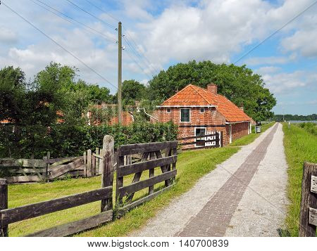 Old Farmhouse of red Bricks behind an old Sea-dyke