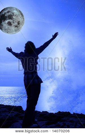 A Woman With Raised Hands Facing A Wave And Full Moon On Cliff Edge