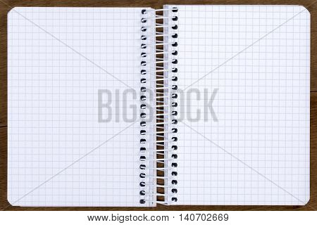 Open blank spiral bound notebook with squared paper on the oak table