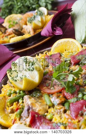 tradirional spanish cuisine paella with mussels and vegetables with starters and wine