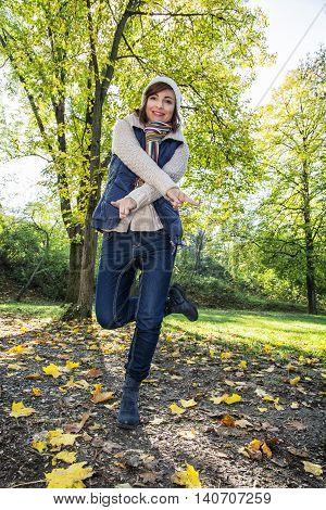 Young caucasian woman posing in autumn nature. Female portrait. Seasonal fashion. Positive emotion. Vertical composition.