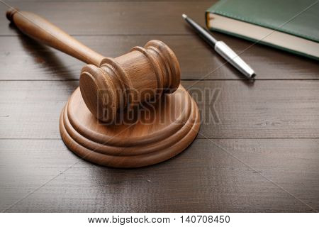 Judge hammer with notepad and pen on brown lacquered wooden desk close up with copy space. Legislation Concept