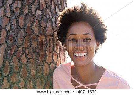 Beautiful Young African Woman Leaning On Tree