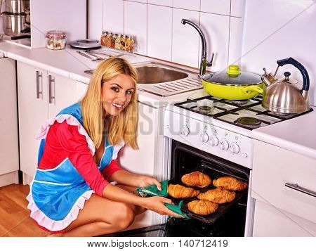 Young woman bake croissants at home kitchen. Woman oven croissants at kitchen. Croissants on breakfast.