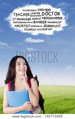 Beautiful female high school student thinking dream jobs while looking up at speech bubble shot outdoors