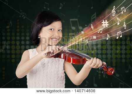 Picture of a pretty Asian girl playing a violin while smiling at the camera