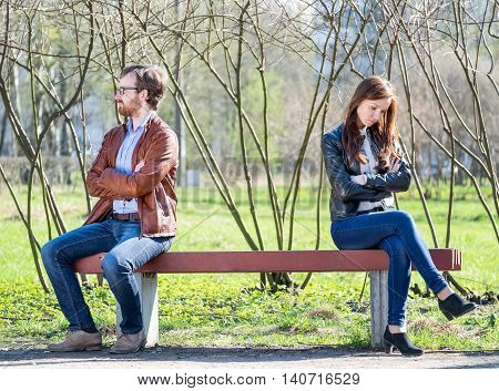Young couple in quarrel sitting on bench