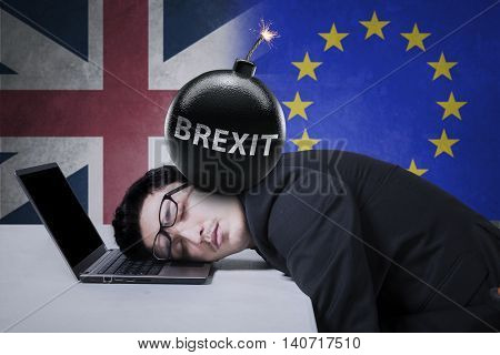 Male worker sleeping on laptop with bomb on his head shot with flag of UK and EU