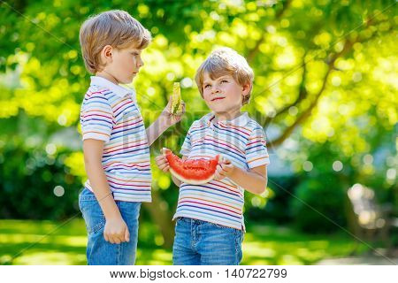 Two little preschool kid boys eating red and yellow watermelon in summer garden. Funny happy children smiling, with healthy fruit snack on sunny day. Siblings, twins and best friends outdoors