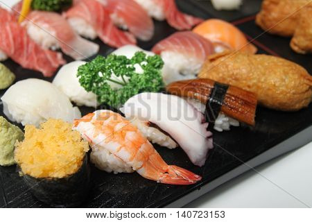 Wooden tray of sushi with shrimp octopus and tuna