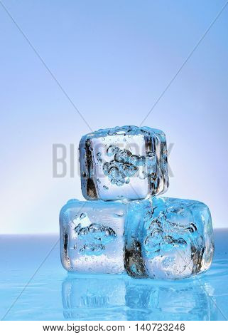 Three ice cubes on glass background, close up