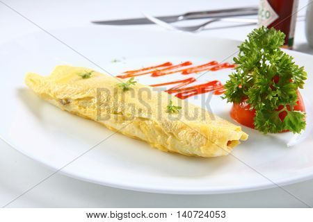 Omelette egg on white plate with chili sauce and herbs